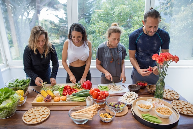 Smiling people cooking vegetables in kitchen Free Photo