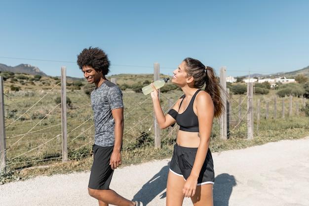 Smiling people walking while woman drinking water Free Photo