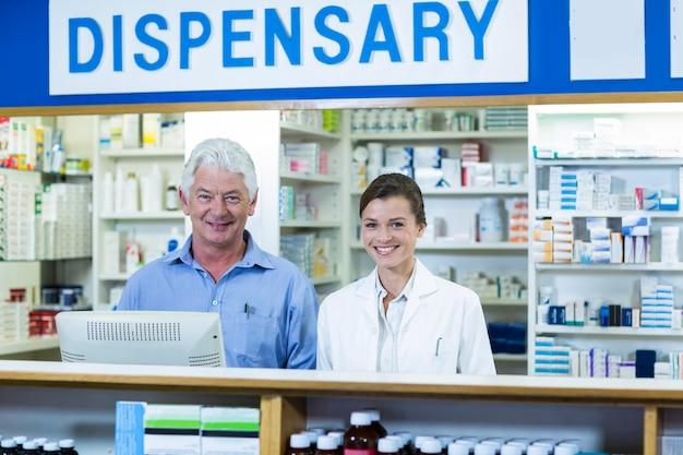 薬局のカウンターに立っている笑顔の薬剤師 Premium写真