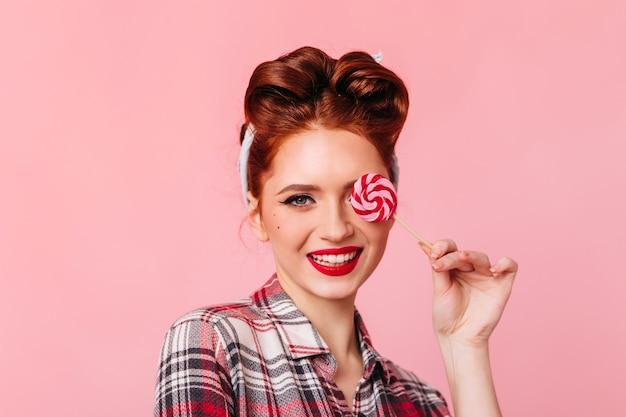 赤いロリポップを食べるピンナップガールの笑顔。ピンクのスペースで隔離の市松模様のシャツを着た女性の正面図。 無料写真
