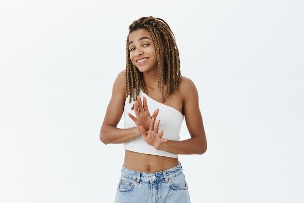 Sorridente educata ragazza afro-americana che rifiuta l'offerta piacevolmente, stringe la mano in segno di diniego o rifiuto Foto Gratuite
