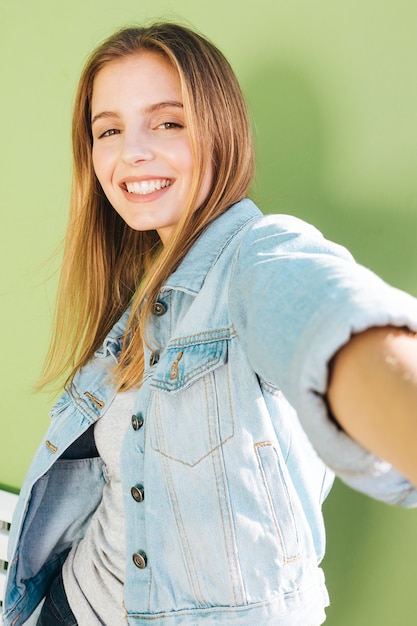 Smiling portrait of a blonde young woman against green backdrop Free Photo