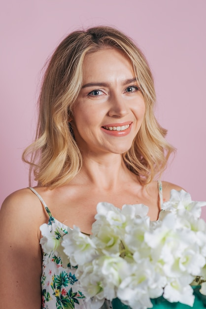 Smiling portrait of blonde young woman holding white fresh flowers against colored background Free Photo