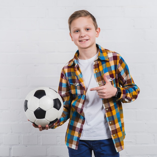 Smiling portrait of a boy showing his soccer ball standing against white brick wall Free Photo