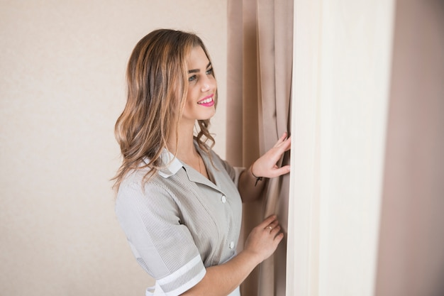 Smiling portrait of a female chambermaid looking out through window Free Photo