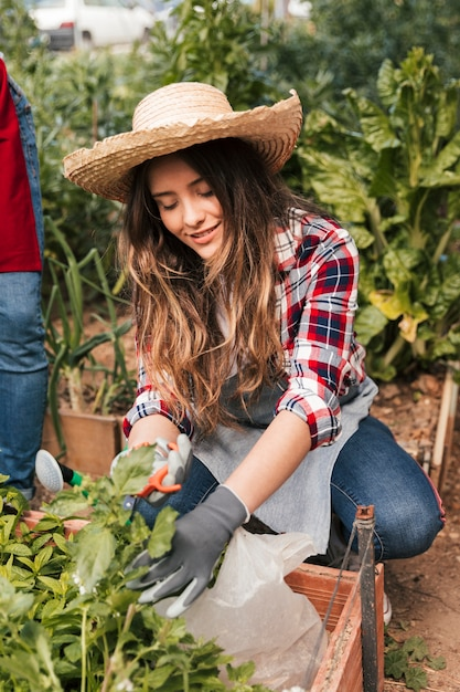 Smiling portrait of a female gardener pruning the plants Free Photo