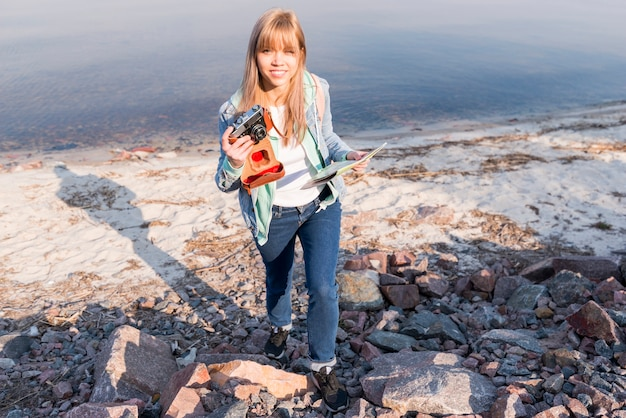 Smiling portrait of a female traveler holding map and camera at beach Free Photo