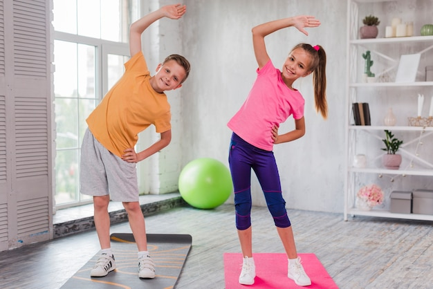 Smiling portrait of a girl and boy standing on exercise mat stretching Free Photo
