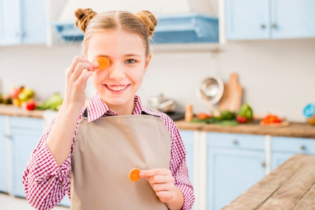 Smiling portrait of a girl covering her one eye with carrot in the kitchen Free Photo