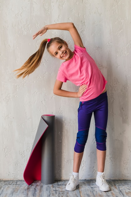 Smiling portrait of a girl doing stretching exercise in front of concrete wall Free Photo