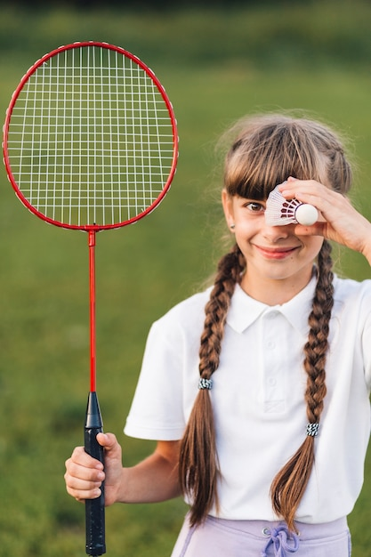 Smiling portrait of a girl holding badminton and shuttlecock over her eyes Free Photo