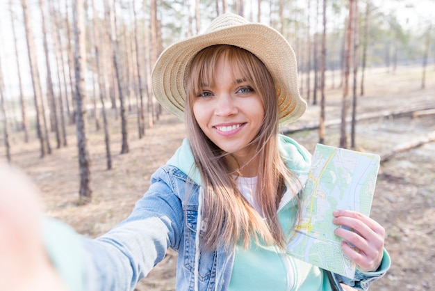 Smiling portrait of a girl holding map in hand taking selfie on mobile phone Free Photo