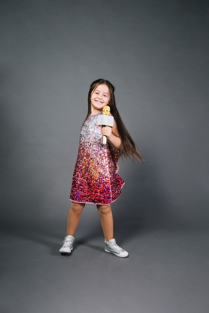Smiling portrait of a girl holding microphone singing song against gray background Free Photo