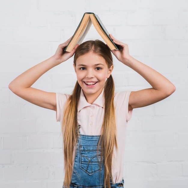4d0a156c2423 Smiling portrait of a girl holding an open book on her head looking to  camera Free