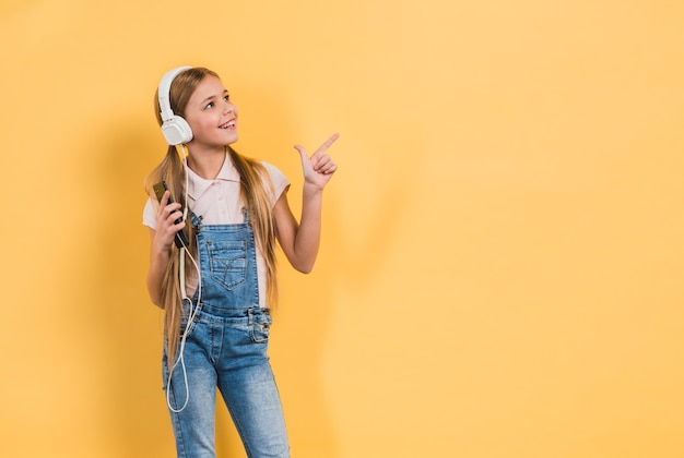Smiling portrait of a girl listening music on headphone pointing at something against yellow background Free Photo