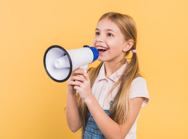 Smiling portrait of a girl shouting into megaphone against yellow background Free Photo