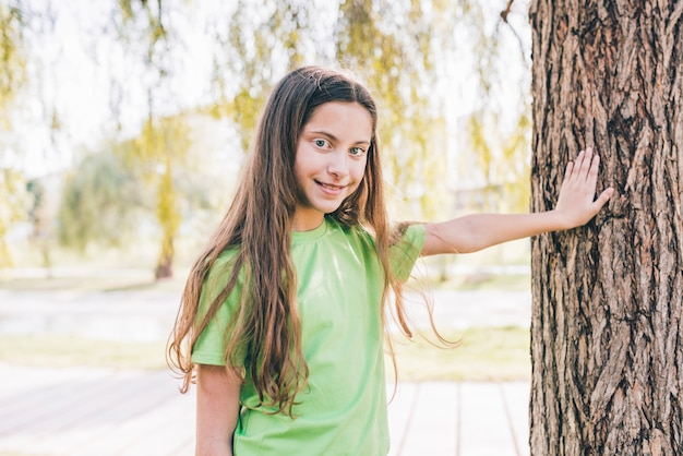 Smiling portrait of a girl touching his hand on tree trunk Free Photo