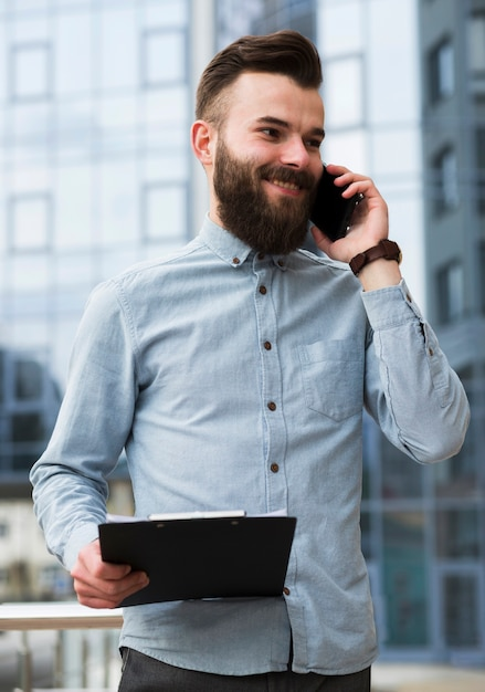 Smiling portrait of a handsome young man holding clipboard in hand talking on mobile phone Free Photo