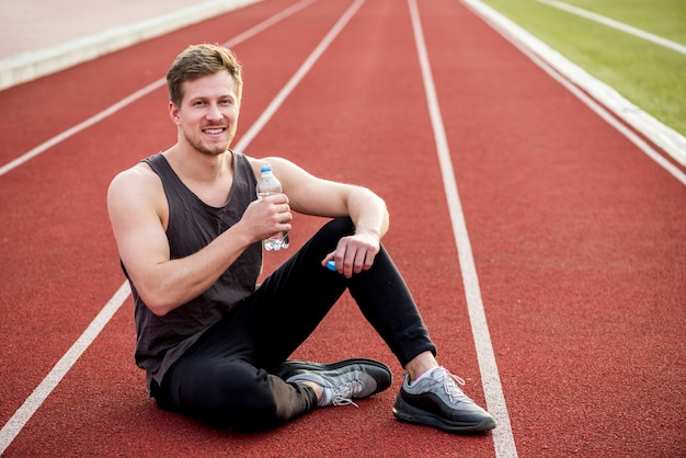 Smiling portrait of a male athlete sitting on race track holding water bottle in hand Free Photo