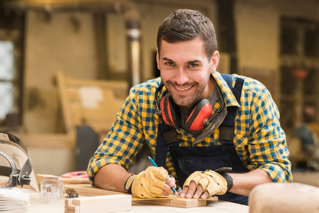 Smiling portrait of a male carpenter taking measurement with ruler and pencil on wooden block Free Photo