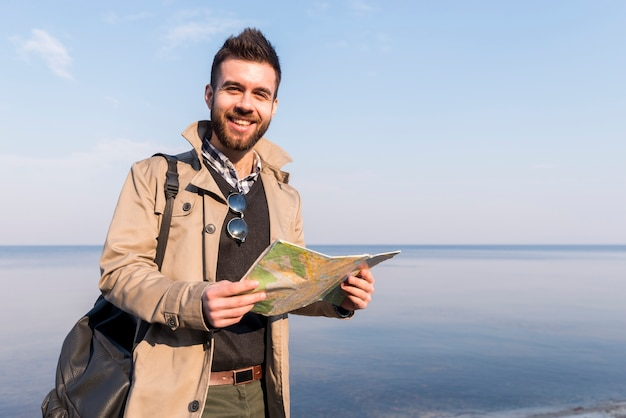 Smiling portrait of a male traveler standing in front of sea holding map in hand Free Photo