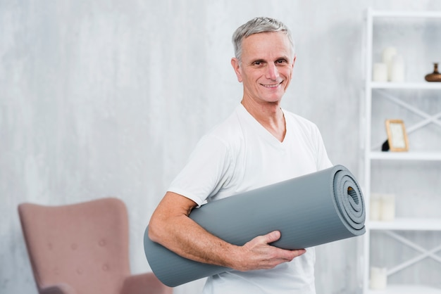 Smiling portrait of a man holding rolled yoga mat at home Free Photo