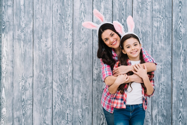 Smiling portrait of mother embracing her daughter from behind in front of wooden backdrop Free Photo