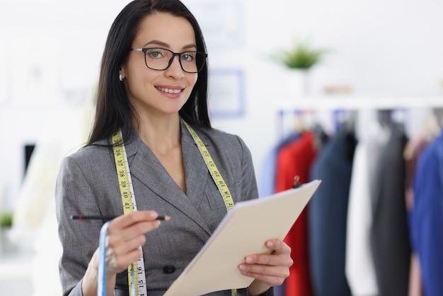 Улыбающийся портрет женщины-дизайнера в ателье. швейные услуги по пошиву одежды concept Premium Фотографии