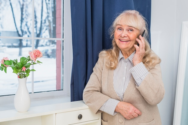 Smiling portrait of a senior woman standing near the window talking on cell phone Free Photo