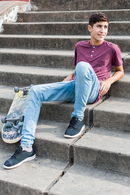 Smiling portrait of a teenage boy relaxing on staircase with skateboard Free Photo