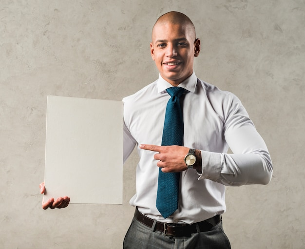 Smiling portrait of a young businessman pointing his finger toward blank placard Free Photo