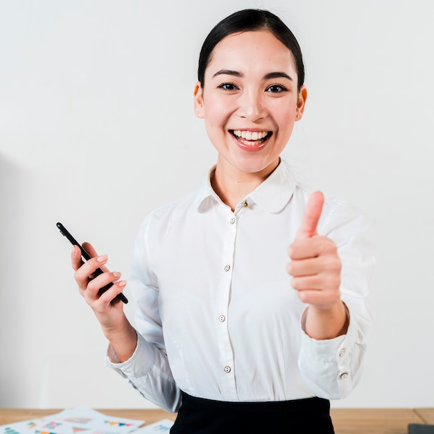 Smiling portrait of a young businesswoman holding mobile in hand showing thumb up sign Free Photo