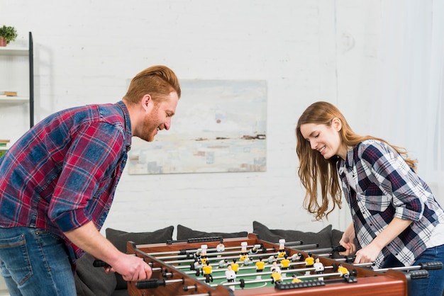 Smiling portrait of a young couple enjoying playing the table soccer game in the living room Free Photo
