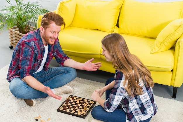 Smiling portrait of young couple sitting on carpet playing the chess Free Photo