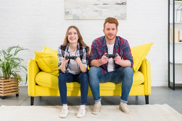 Smiling portrait of young couple sitting on yellow sofa playing games with video game console Free Photo