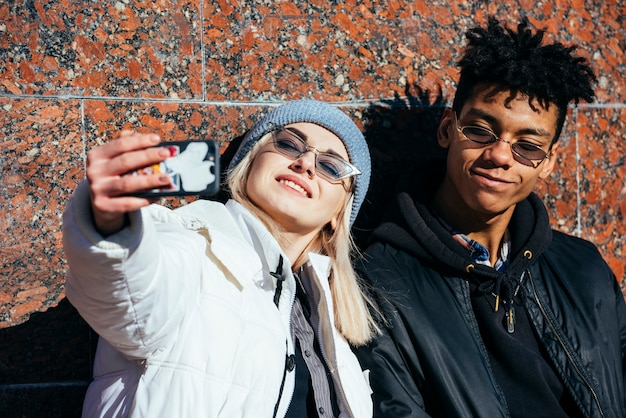 Smiling portrait of a young couple taking selfie on mobile phone Free Photo