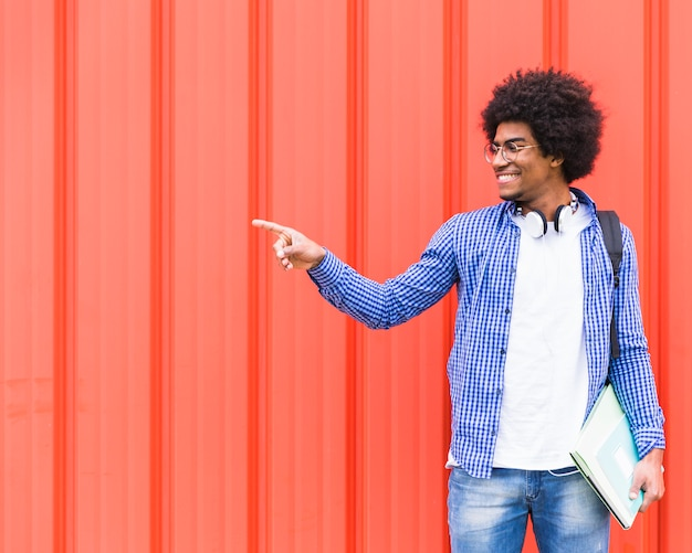 Smiling portrait of a young male student pointing finger at something standing against red wall Free Photo