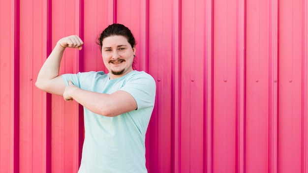 Smiling portrait of young man flexing his muscle against red corrugated wall Free Photo
