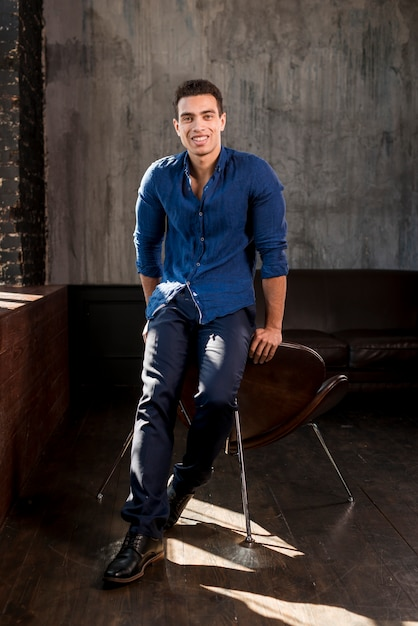 Smiling portrait of a young man leaning on chair looking at camera Free Photo