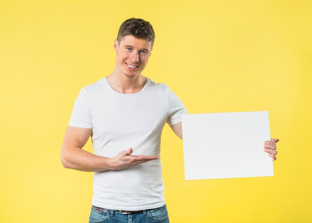 Smiling portrait of a young man presenting something on white blank card against yellow backdrop Free Photo