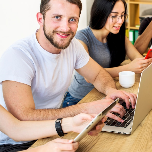 Smiling portrait of a young man working on laptop over wooden desk Free Photo
