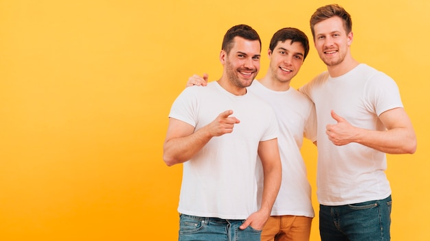 Smiling portrait of a young three male friends standing against yellow background Free Photo
