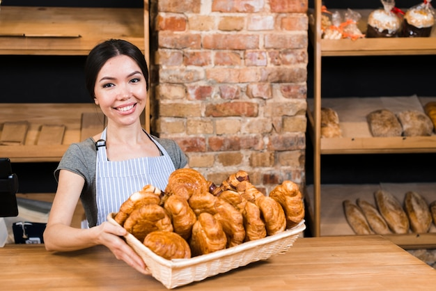 Smiling portrait of a young woman holding fresh baked croissant basket in the bakery shop Free Photo