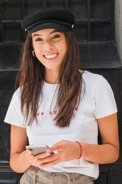 Smiling portrait of a young woman holding mobile phone in hand looking at camera Free Photo