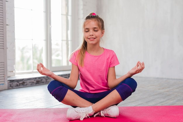 Smiling portrait of a young woman sitting on pink carpet doing meditation Free Photo