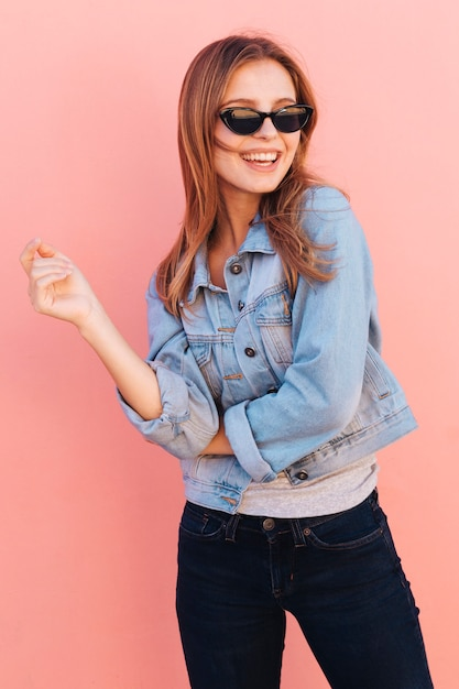 Smiling portrait of a young woman wearing sunglasses against pink backdrop Free Photo