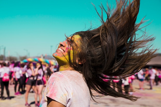 Smiling portrait of a young woman with holi color tossing her hair Free Photo