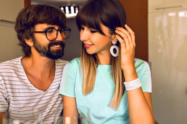 愛の肯定的なカップルの笑顔、ハンサムなひげの男と彼のロマンチックな夜、エレガントな服、暖かい色、モダンなインテリアを楽しんでいる彼のエレガントな妻。 無料写真