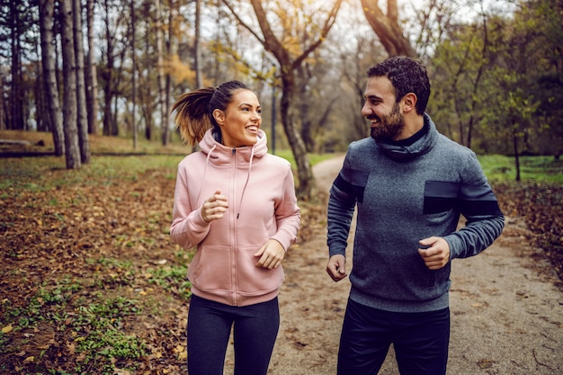 Smiling positive dedicated couple in sportswear looking at each other and running in nature. Premium Photo