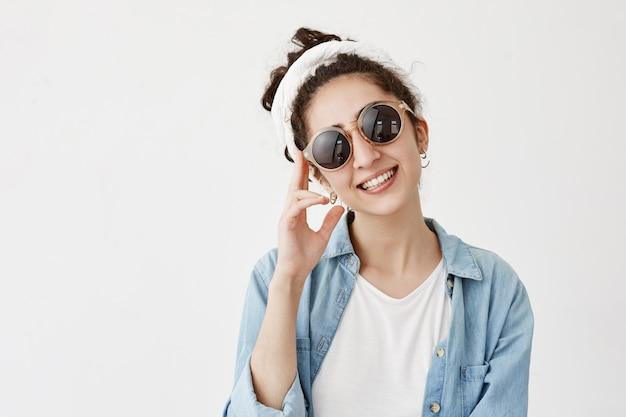Улыбающаяся позитивная женская модель в модных круглых солнечных очках с тряпкой в джинсовой рубашке, имеет хорошее настроение, демонстрирует белые зубы, рада знакомству с близкими. счастье, концепция выражения лица Бесплатные Фотографии